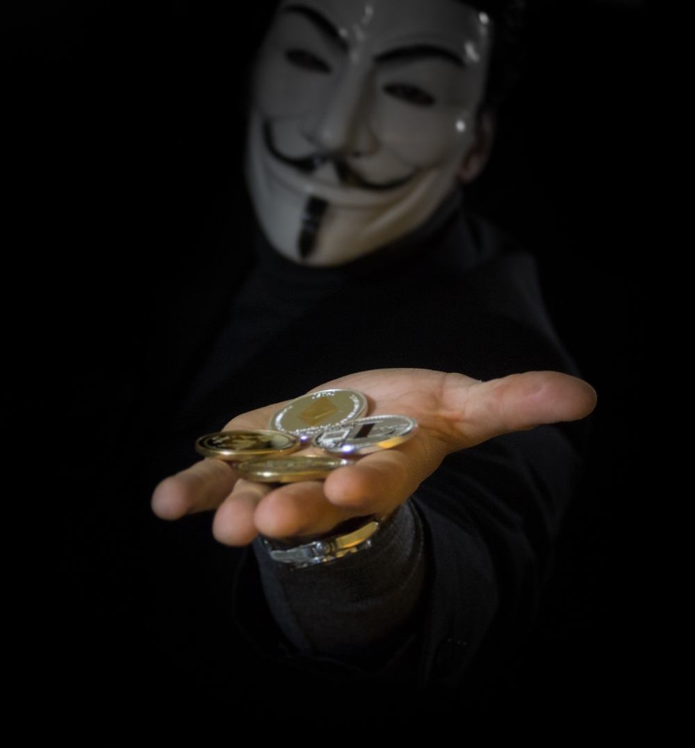 Bitcoin Kurs Prognose Bitcoin Münze auf Hand eines Mann mit einer Anonymous Maske