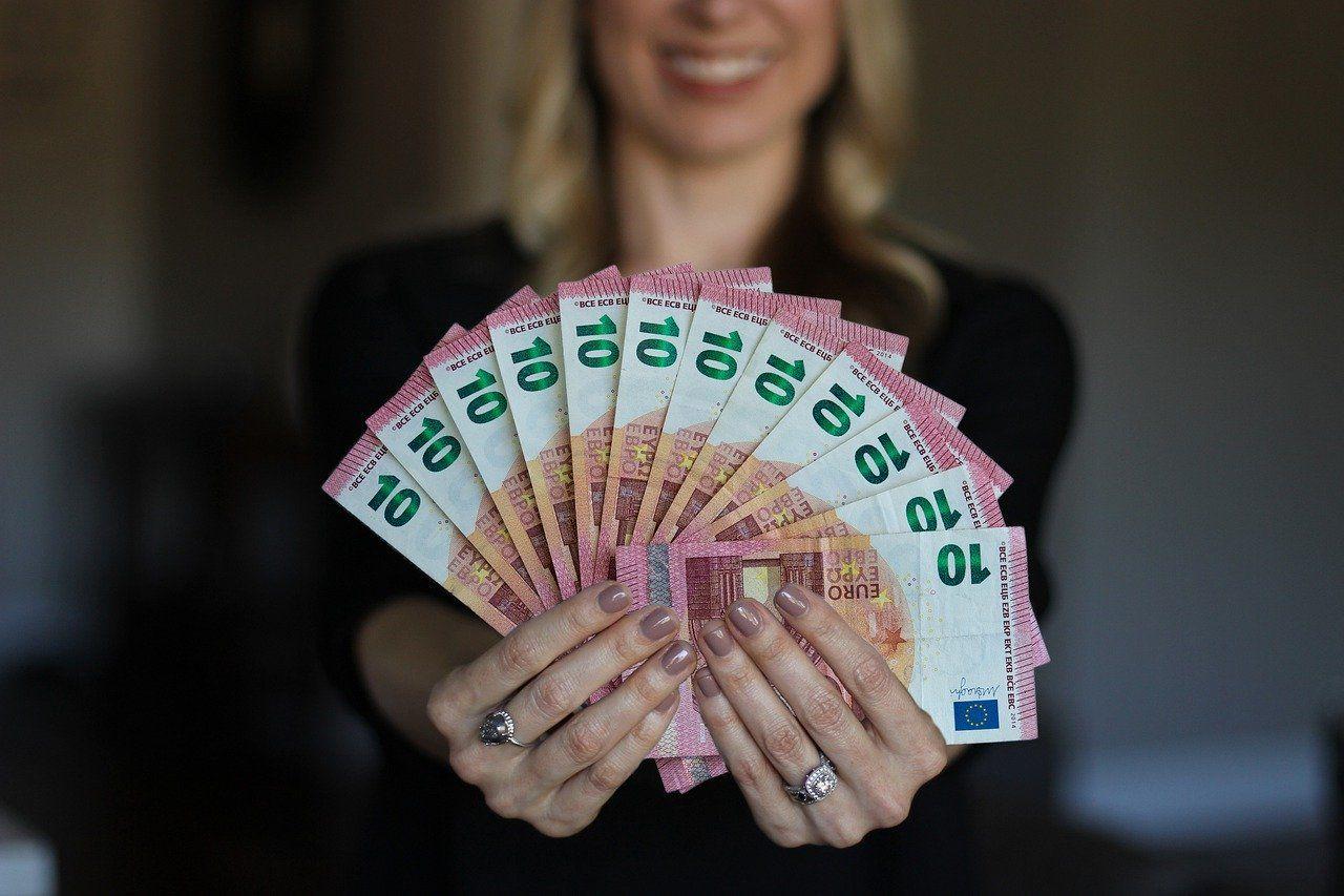 Youhodler Frau hält 10€ Banknoten in den Händen